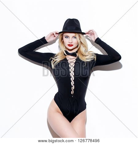 Sexy blonde female performer in hat and tuxedo isolated on white