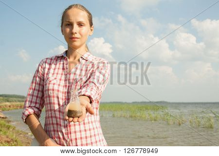 Water Purity Test. Woman holding a chemical flask with water, lake or river in the background.