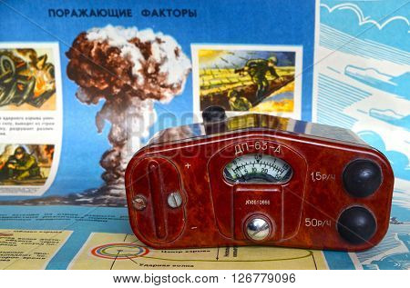 ILLUSTRATIVE EDITIRIAL.Vintage Soviet military radiometer DP-63-A.Background - poster Soviet Civil Defense: Atomic weapon.At April 19,2016 Kiev, Ukraine