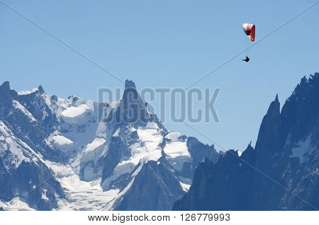 Paragliding flying over Mont Blanc Massif, in the background is Dent du Geant, Alps, Chamonix, France