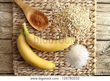 Top view of ingredients of diet cookies - banana, oatmeal, sugar and cinnamon on a stand made of rattan.