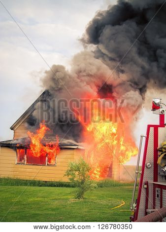 Black smoke and red hot flames  on a house
