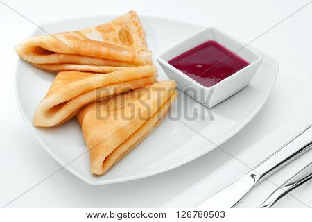 close up view of nice yummy crepes with jam on white  table