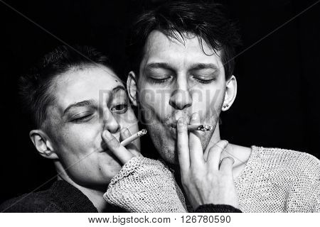 Studio portrait of a young man and woman smoking cigarettes