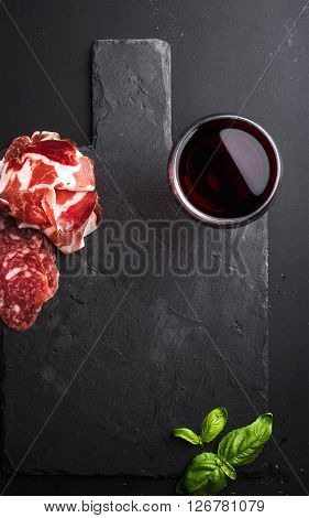 Glass of red wine, meat appetizer and basil on black  slate stone board over dark background. Top view, copy space