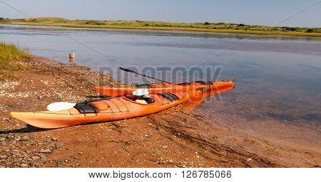 Pair of orange kayaks by the water in prince edward island