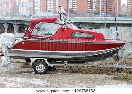Red motor boat loaded on the trailer for transportation.