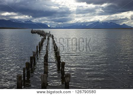 Derelict wooden pier stretching out into the sea at Puerto Natales in Patagonia, Chile.