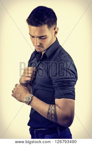 Handsome young man in blue shirt and jeans posing on light background in studio, looking down