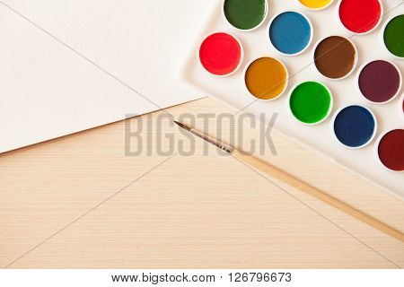 Artist's work space. Set of watercolor paints in white base sheets of white watercolor paper brush on light woden background. Artistic background.