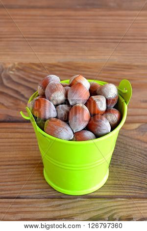 Hazelnuts in a small green bucket on a wooden table. Product contains proteins and vitamins