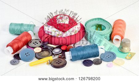 various tailoring tools for the repair of clothing buttons threads needles pillow tailoring meter a thimble on white fabric