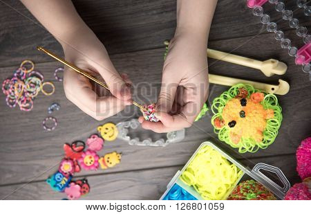 Children's Hands Are Weaving Figures Out Colored Rubbers