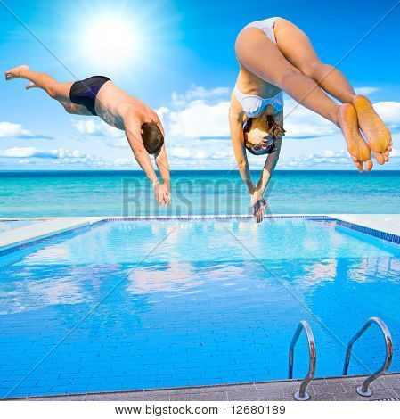 woman and man - simultaneously diving into pool