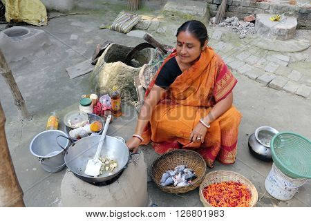 KUMROKHALI, INDIA - FEBRUARY 13: Traditional way of making food on open fire in old kitchen in a village, Kumrokhali, West Bengal, India February 13, 2014.