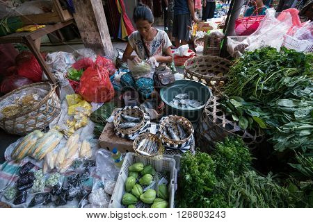BALI, INDONESIA - MARCH 16, 2016: Commercial activities in the main Ubud market in the morning, showing trader selling vegetables. Agricultural produce comes direct from the farmers here in Bali.