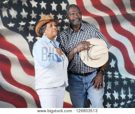 A mature African American cowboy couple honoring their country with hands over their hearts.  They stand proudly before the stars and stripes.