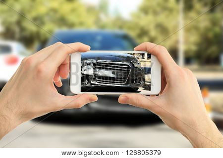 Man photographing his car with damages