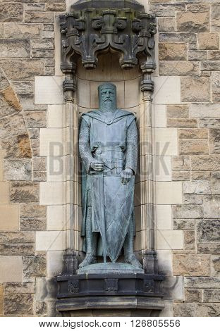 A statue of Sir William Wallace on the facade of Edinburgh Castle in Scotland.