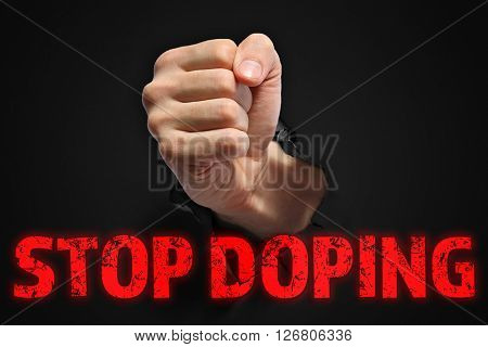 Stop doping concept. Man fist punching through black paper