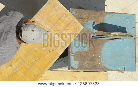 Carpenter cutting wooden planks with table saw
