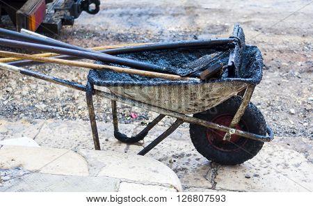working tools for repairing city roads with bitumen and asphalt mix. wheelbarrow shovel rake