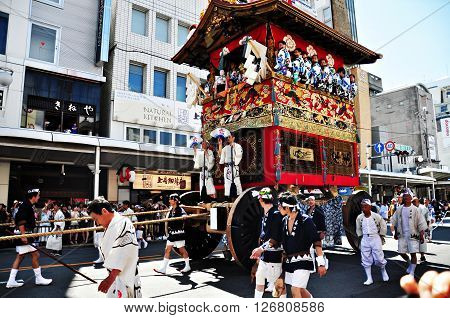 Kyoto Japan - July 17, 2011: A highly decorated float along with its accompanying men in traditional Japanese clothes is being dragged in a parade during the Gion Matsuri of July 17th 2011 in Kyoto Japan.