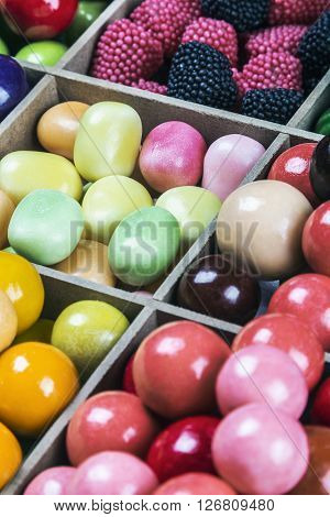 assortment of candy and gum in a wooden box. focus in the center of the frame