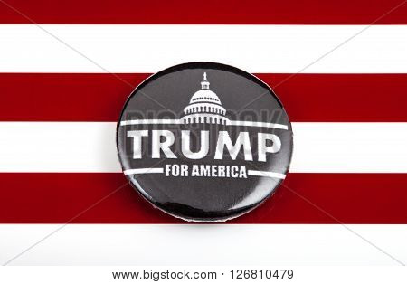 LONDON UK - MARCH 3RD 2016: A Trump 2016 pin badge over the US flag symbolizing the Donald Trump campaign to become the next President of the United States 3rd March 2016.
