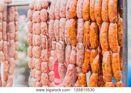 Traditional food. Smoked sausages meat hanging background