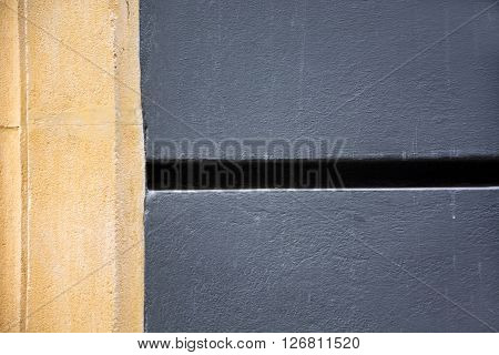 A original and elegant photo of a detail of a building facade with grey colour, brown colour and sunlight