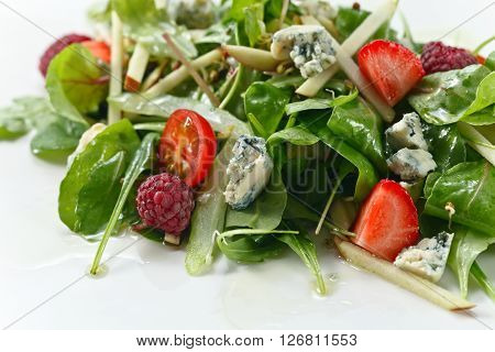 green salad with Gorgonzola and berries on white plate