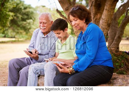 Senior man and woman learning internet and mobile phones: young kid helping his grandparents surfing the web with their new mobile phones. All people hold a tablet and type on screen