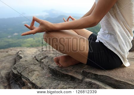 young woman practice yoga at mountain peak cliff
