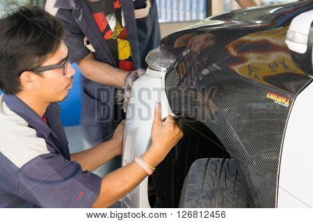 Bangkok Thailand - November 21 2015 : Unidentified repairman working for repair a car bumper part in Thai garage
