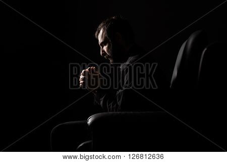 Man with Beard Sitting on a Armchair Praying