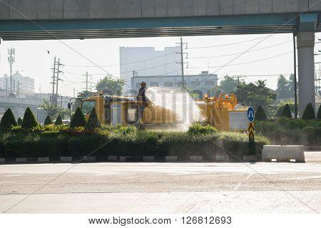Bangkok Thailand - November 21 2015 : Unidentified Bangkok Metropolitan Administration worker working for watering the lawn on road by water tanker truck in Bangkok Thailand.