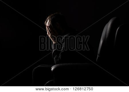 Desperate Man with Hands on His Face Sitting on an Armchair