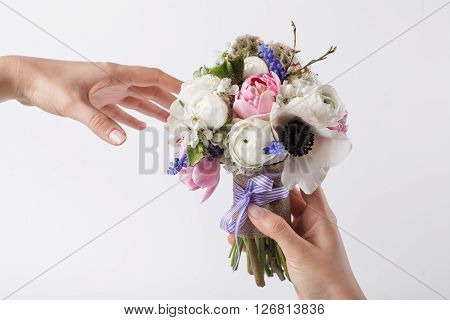 One hand is giving spring bouquet from pink tulips violet grape hyacinths white anemones violet veronica and white buttercup with violet ribbon to the other hand