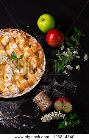 Delicious homemade rustic half-closed apple pie with fresh apples and apple-tree flowers on black background. Contrast vintage image. Top view