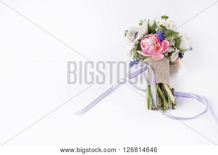 Pastel bouquet from pink tulips violet grape hyacinths white anemones violet veronica and white buttercup with violet ribbon lying on white background