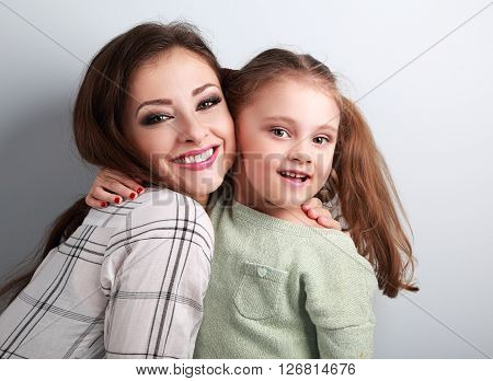 Happy Smiling Mother Cuddling Playful Emotional Fun Daughter In Studio On Blue Background. Closeup P