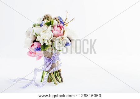 Bouquet from pink tulips violet grape hyacinths white anemones violet veronica and white buttercup with violet ribbon standing on white background left side
