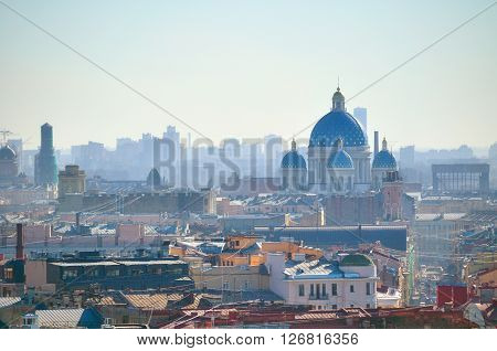 Architectural landscape. Birds eye view of Saint-Petersburg roofs and Holy Trinity Izmailovo Cathedral under soft sunlight. Focus at the cathedral. Soft filter applied.