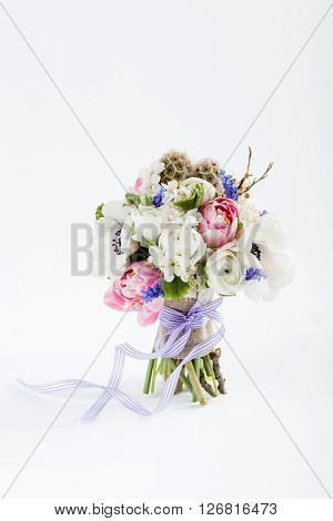 Bouquet from pink tulips violet grape hyacinths white anemones violet veronica and white buttercup with violet ribbon standing on white background