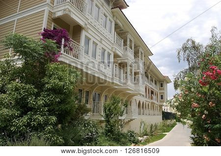 Side, ANTALYA, TURKEY - JUNE 02, 2015: Original building and walkway with flowers in high class hotel Ali Bey Resort, Turkey.