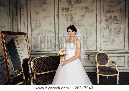 Portrait of young beautiful bride near the sofa. Wedding makeup wedding hairstyle Wedding dress. Gorgeous young bride at interior