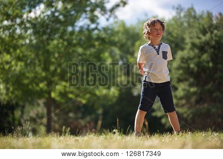 Boy standing alone at the park day dreaming