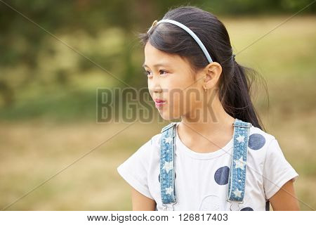 Asiatic girl with diadem and suspenders looks sceptical