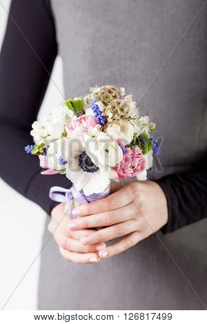 Woman in grey dress and black shirt is holding a spring bouquet from pink tulips violet grape hyacinths white anemones violet veronica and white buttercup with violet ribbon